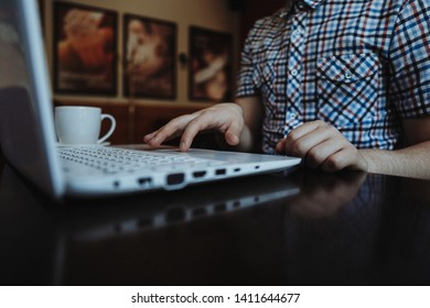 Close-up of a man working on a laptop in coffeehouse