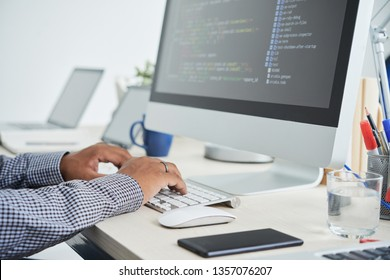 Close-up of man working as programmer, he sitting in front of monitor and typing on computer keyboard
