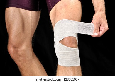 Closeup of man wrapping knee with sports wrap on black background
