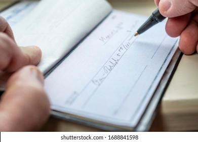 Closeup of a man writing a check.