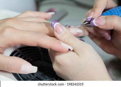 Closeup of manicurist cleaning female finger nails with a drill tool