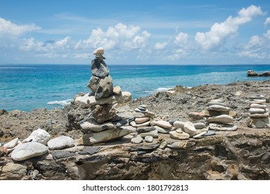 Close-up of manmade cairns Caribbean Sea coastline with blue sea background on a sunny day in Frederiksted in the US Virgin Islands
