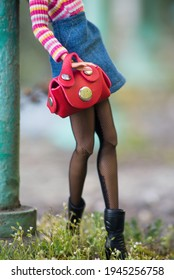 Nahaufnahme von Puppenbeinen mit blauem Jeanrock, sexy Oberschenkeln und rotem Lederhandtasche auf der Straße