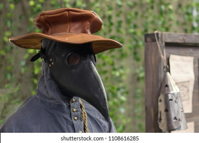 Close-up of mannequin wearing black plague doctor mask and brown hat