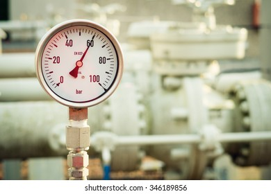Closeup of manometer, measuring gas pressure. Pipes and valves on the background. Selective focus.