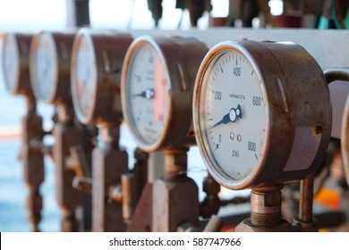 Closeup of manometer, measuring gas pressure. Pipes and valves at industrial plant.Pressure gauge, measuring instrument close up on oil and gas pipeline.