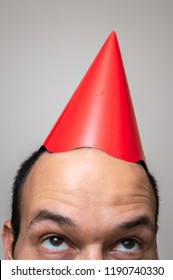 Closeup of a man's face looking up at the red birthday hat on the top of his head