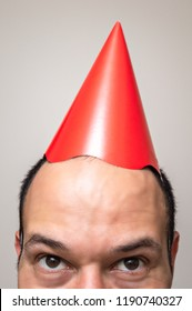 Closeup of a man's face with red birthday hat on the top of his head