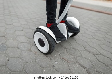 Closeup of a man's feet on a modern hoverboard. Stylish guy in jeans in sneakers standing on a white hoverboard in the city on a summer day.