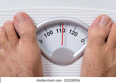 Closeup of man's feet on weight scale