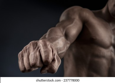 Close-up of a man's fist. Strong and power man's hand with muscles and veins. Studio shooting. Mans hand