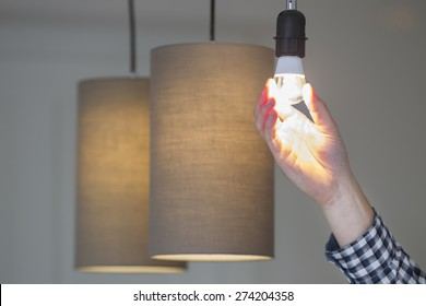 Closeup of man's hand adjusting electric bulb by pendant lights at home