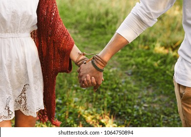 Close-up of a man's hand with bracelets leads the girl's hand in a red knitted Cape and a white dress on the green grass