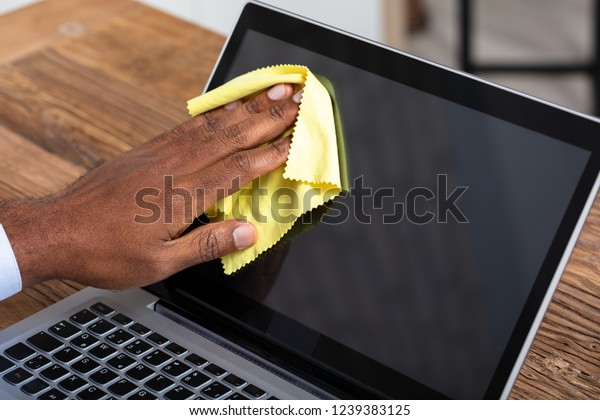 Close-up Of A Man's Hand Cleaning Laptop Screen With Yellow Cloth