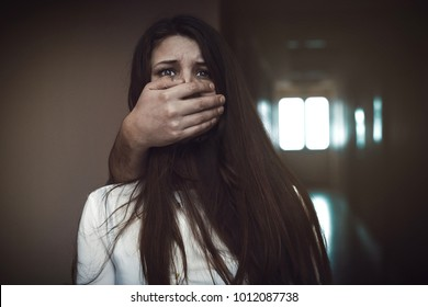 Closeup of a mans hand covering a womans mouth. Concept of domestic violence or kidnapping