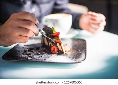 Close-up of man's hand eating cake with fork