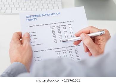 Close-up Of Man's Hand Filling Customer Survey Form