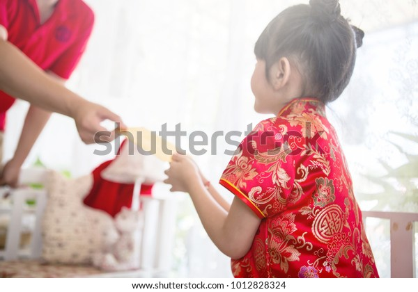 Closeup of the man's hand giving a golden envelope with money to a girl in cheongsam dress on Chinese New year celebration.