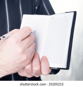 Closeup of mans hand going to write a business plan