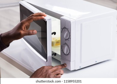 Close-up Of A Man's Hand Heating Food In Microwave Oven