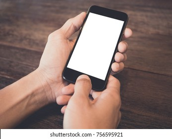 Closeup of man's hand is holding a black cell phone with blank white screen that you can put any ideas in this space on wood table at coffee cafe