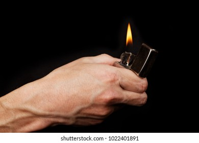 Closeup mans hand holding a burning metal gasoline lighter. Isolated on black.