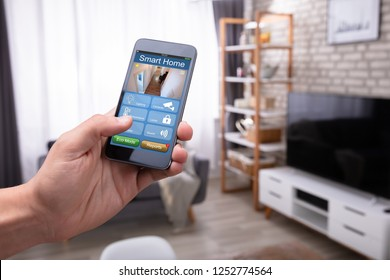Close-up Of A Man's Hand Holding Cellphone With Smart Home Application At Home