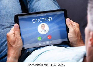 Close-up Of A Man's Hand Holding Digital Tablet With Doctor's Incoming Call On Display
