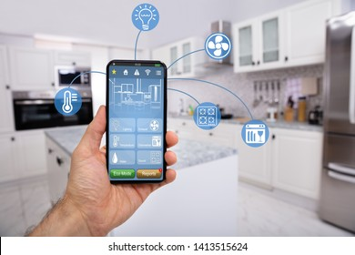 Close-up Of Man's Hand Holding Mobile With Smart Home Control Icon Feature With Kitchen Background