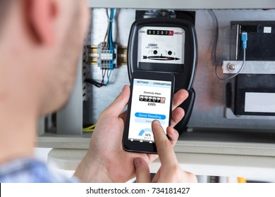 Close-up Of A Man's Hand Holding Mobile Phone Reading Electric Meter