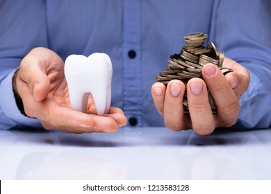 Close-up Of A Man's Hand Holding White Tooth And Golden Coins Over Desk