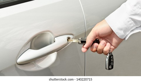 Closeup of a man's hand inserting a key into the door lock of a car