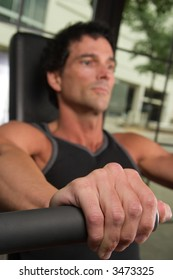 Closeup of a man's hand on an arm exercise machine in a fitness center.  The hand is in clear focus with shallow depth of field causing the man's face to be out of focus.