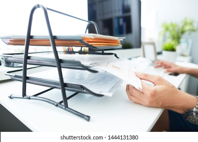 Close-up of a man's hand pulling files from office shelves. White collar job, digital shopping, office lifestyle, search success, enter login, password and credentials concept.