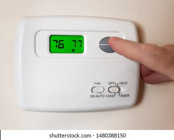 Closeup of a man's hand setting the room temperature on a programmable home thermostat.