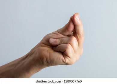 Close-up Of Man's Hand Snapping His Finger Against Gray Background