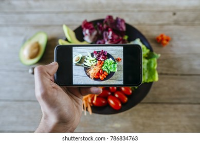 Close-up of man's hand taking a picture with a smartphone to a salad
