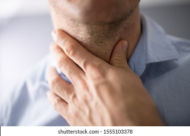 Close-up Of A Man's Hand Touching His Sore Throat