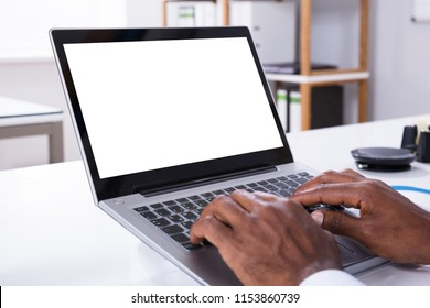 Close-up Of Man's Hand Typing On Laptop Over The White Desk