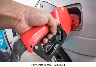 Close-up of a man's hand using a petrol pump to fill-up his car with fuel