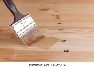 close-up of a man's hand varnishing a wooden table