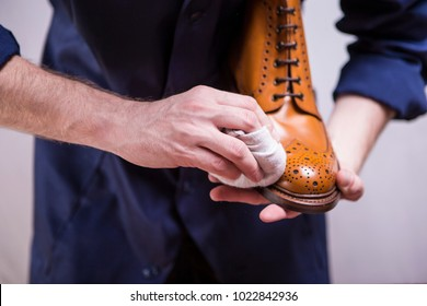Closeup of Mans Hands with Cleaning Cloth for Premium Derby Boots. Horizontal Image Composition