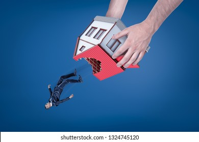 Close-up of man's hands holding house with hole in roof upside down and dropping out little businessman. Real estate scam. Eviction of tenant. Housing issues.