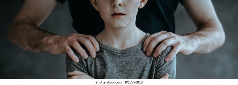 Close-up of man's hands on a boy's arms. Concept of pedophilia.