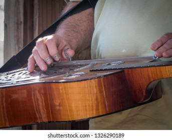 Closeup of a man's hands playing a brown wooden dobro