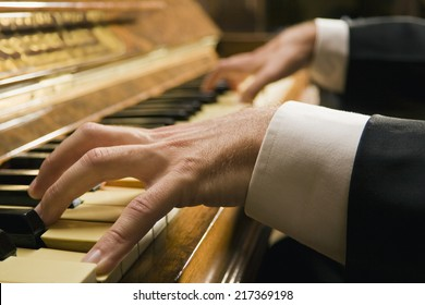 Close-up of a man's hands playing a piano