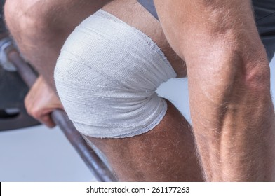 Closeup of man's knee wrapped in sport bandage while attempting to lift heavy weights on barbell in gym