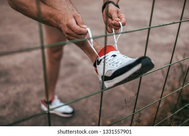 Close-up of a man's leg tying shoelaces on shoe, in summer in the city about a fence or fence. Sports lifestyle workout, jogging in morning in evening, guy doing fitness.