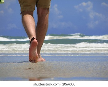 Closeup of a man's leg walking on new smyrna beach, florida.