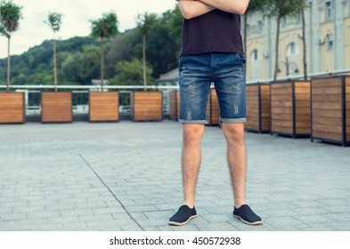 Close-up of a man's legs in denim shorts. Jeans clothes.